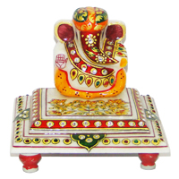 Marble ganesh idol sporting a turban and sitting on chowki